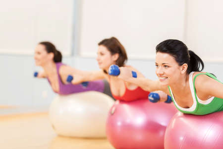 fit ball: women working out in gym doing pilates. group of young girls lying on balls and holding dumbbells