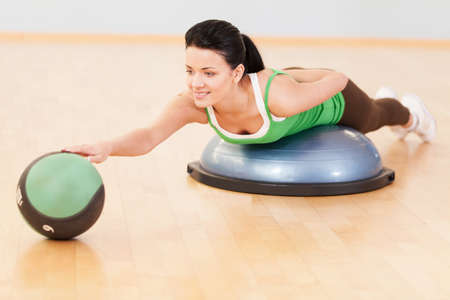 beautiful sporty woman doing exercise on ball. young woman doing exercise on fitness ball and touching ball photo