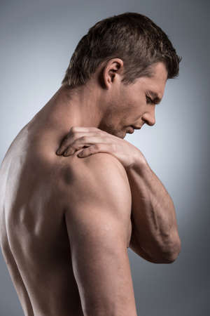 convulsions: Close-up of young shirtless man with shoulder pain. young man standing on grey white background