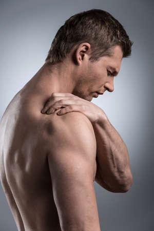 luxacion: Primer plano de hombre sin camisa joven con dolor en el hombro. joven de pie sobre fondo blanco gris
