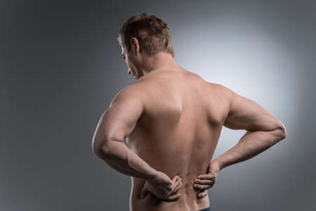 Close-up of young shirtless man with back pain. young man standing on grey white background photo