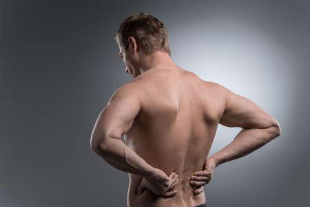 dolor de espalda: Primer plano de hombre sin camisa joven con dolor de espalda. joven de pie sobre fondo blanco gris