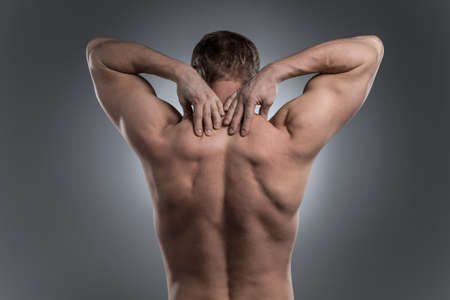 man back pain: Close-up of young shirtless man with neck pain. young man standing on grey white background