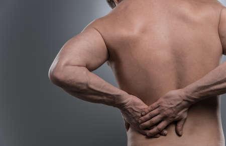 luxacion: espalda del hombre descamisado joven con dolor de espalda. joven de pie sobre fondo blanco gris Foto de archivo
