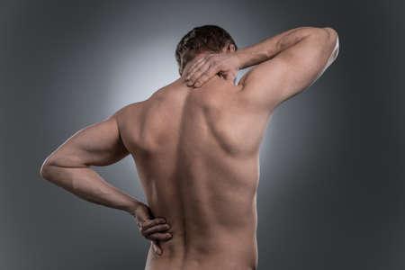 luxacion: vista trasera del hombre descamisado joven con dolor de cuello. joven de pie sobre fondo blanco gris