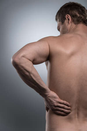 back view of young shirtless man with back pain. young man standing on grey white background photo