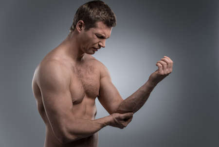 stretching condition: young man having pain in his elbow. Acute pain in man elbow on silver background.