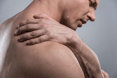 luxacion: perfil del hombre descamisado joven con dolor en el hombro. joven de pie sobre fondo blanco gris