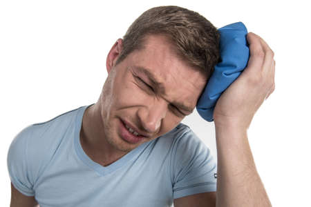 closeup of man head holding icepack on his head. young man experiencing pain on white background photo
