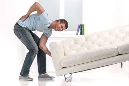 dolor muscular: Hombre hermoso que levanta sofá y sentir dolor. hombre droped sofá causa de espalda dolorosa