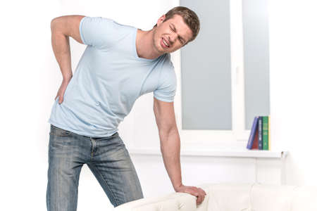 Handsome man leaning on sofa and feeling pain. man on sofa because of painful back Foto de archivo