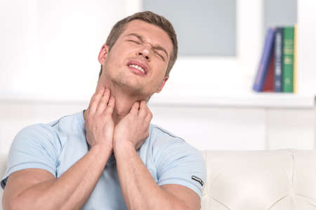 Portrait of handsome male with pain in throat. Man suffering from throat problems on white sofa