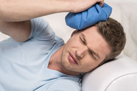 closeup of man holding icepack on his head. young man experiencing pain on white sofa photo
