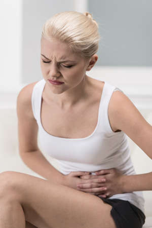 Woman having abdominal pain on sofa. blond girl with upset stomach or menstrual cramps  photo