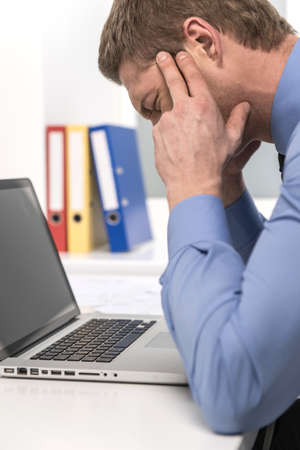 handsome man under stress, fatigue and headache. Businessman suffering from headache at office  photo