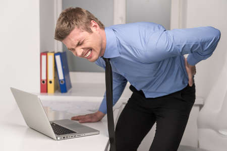persona malata: bell'uomo sensazione di dolore in schiena. Imprenditore che soffrono di mal di schiena in ufficio Archivio Fotografico
