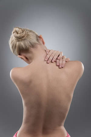 collo: Donna che massaggia dolore al collo e schiena. giovane donna con dolore isolato su bianco
