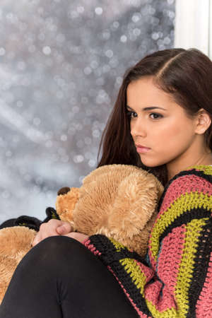 Portrait of pretty girl in sweater holding toy. Sad girl holding teddy bear  photo