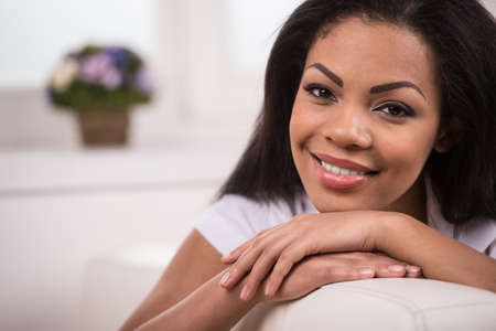 Beautiful youthful African American woman. Girl relaxing at home on grey couch wearing rose shirt photo