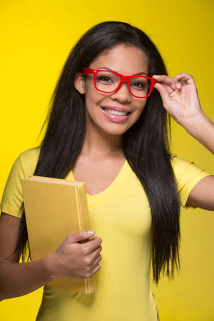 Closeup portrait of young smiling woman. student wearing red glasses, holding book photo
