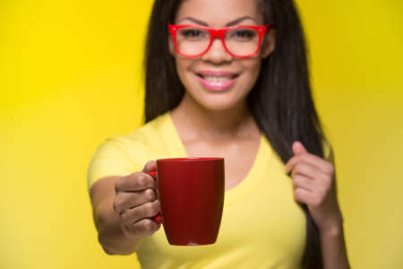 Closeup portrait of young happy woman. student wearing red glasses, giving cup photo
