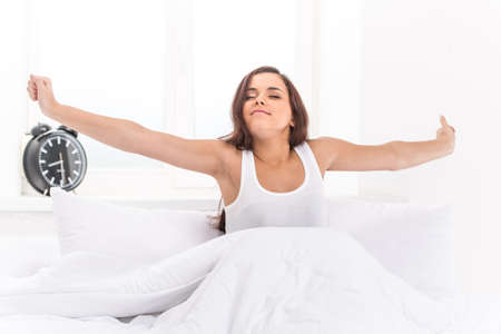 Beautiful young girl lying in bed. Young beautiful, woman waking up fully rested.  Stock Photo