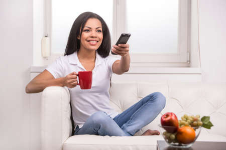 american content: Woman watching tv at home and holding a remote control. Smiling woman on couch changing TV programme