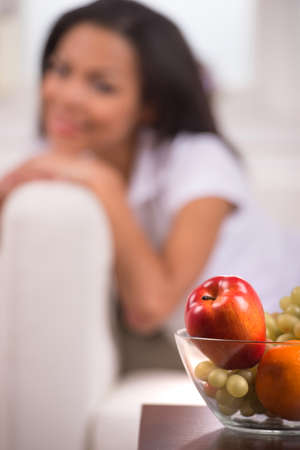 blurred image of African American woman. Girl relaxing at home on grey couch with apple on foreground photo