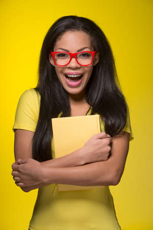 casuals: Closeup portrait of young laughing woman. student wearing red glasses, holding book