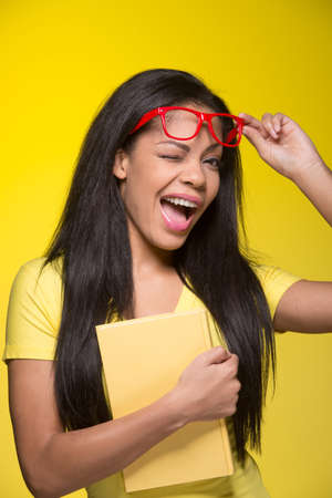 Closeup portrait of young winking woman. student wearing red glasses, holding book photo