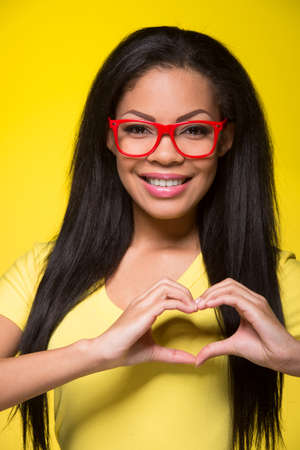 casuals: Closeup portrait of young happy woman. student wearing red glasses, showing heart sign