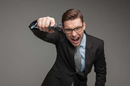 angry businessman: Angry criminal businessman with gun on grey background. angry boss shouting at camera and aiming gun