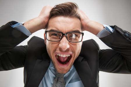 Close-up portret van boos, gefrustreerd man, trekt zijn haar uit. Negatieve menselijke emoties en gezichtsuitdrukkingen Stockfoto