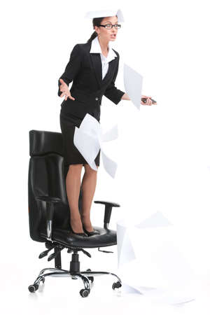 angry businesswoman shouting when standing on chair. woman wearing suit and throwing paper on white