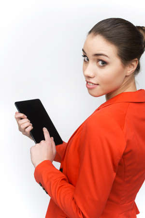 over the shoulder view: Young woman using touch pad on white background. Over shoulder view of woman holding tablet and looking back