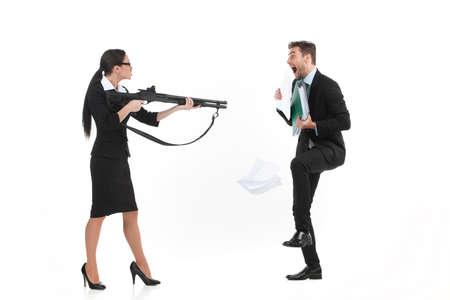 mujer con pistola: reñir entre el hombre y la mujer sobre fondo blanco. vista lateral de la mujer de pie y apuntando al hombre con arma