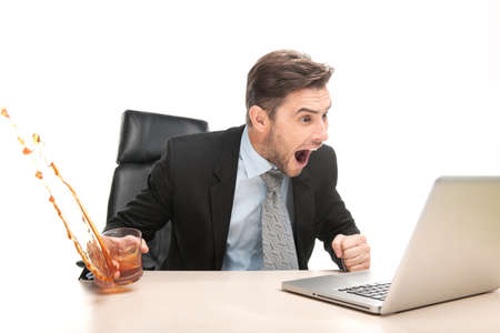 businessman working at his computer: Angry businessman working at his laptop computer. man sitting on chair with glass and drinking alcohol Stock Photo