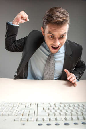 angry man hammering on table before computer. closeup of young businessman frustrated and furious about business photo