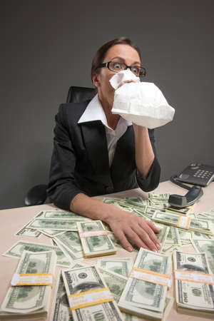 Closeup of businesswoman sitting at table and holding bag to mouth. tired and sick woman sitting at the table covered with money photo