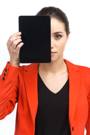 Woman holding up blank tablet computer. Girl obscuring half of her face with screen photo