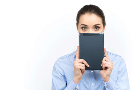 obscured face: young woman looking out of digital tablet. beautiful girl holding tablet over her face on white background