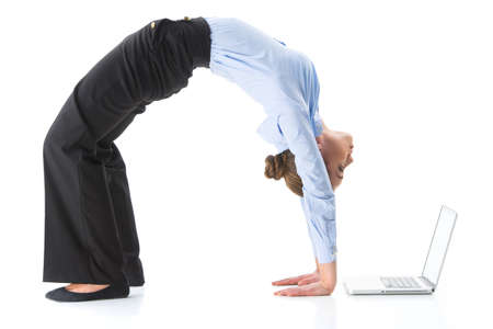 Woman doing crab yoga pose in studio. Woman exercising and looking at computer screen