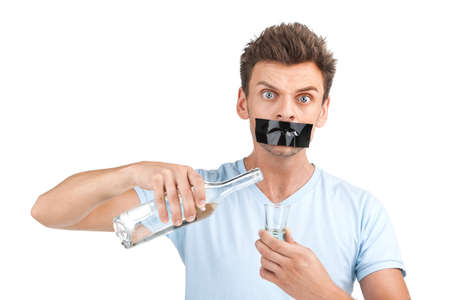 drinking problem: young man wants to stop drinking. Man with bottle of alcohol and tape over mouth.  Stock Photo