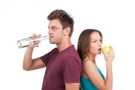 alcoholismo: joven y la mujer con agua y la manzana. hombre adicto pie sobre fondo blanco
