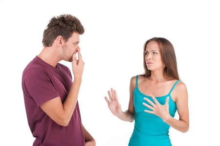 Disgusted woman looking at young man. man standing with finger in nose on white background