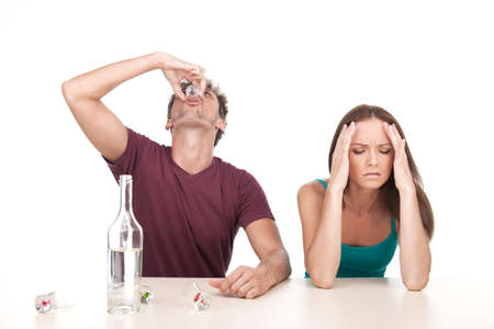 alcoholic man: Man drinking alcohol and woman sitting upset at table. Photo of woman with alcoholic husband on white background Stock Photo