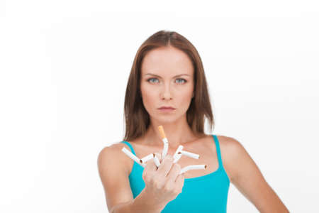 breaking up: young woman breaking up cigarette isolated on white background. Young pretty woman stops smoking and breaking cigarettes Stock Photo