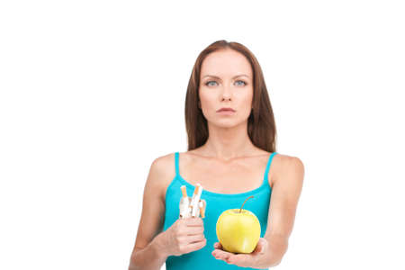 quiting: serious looking woman refusing cigarette. girl choosing apple over white background  Stock Photo