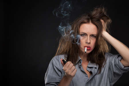 black girl smoking: Portrait of exhausted female holding cigarette. bad looking woman smoking cigarette on black background