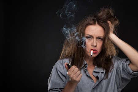chica fumando: Retrato de agotado celebración cigarrillo femenino. mal aspecto cigarrillo mujer que fuma en fondo negro